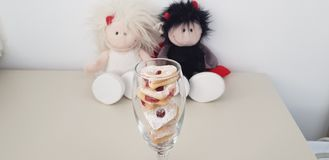 Wine glass with heart shaped cookies near couple of soft toys royalty free stock photography