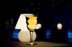Wine glass and lamp. Romantic evening in restaurant with white wine and lamp royalty free stock images