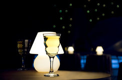 Wine glass and lamp. Romantic evening in restaurant with white wine and lamp royalty free stock photography
