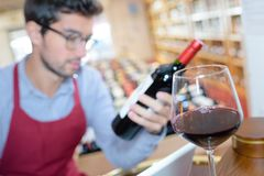 Wine glass with liquor store seller in background. Wine glass with liquor store seller in the background Stock Photography