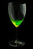A wine glass with a mystic fluid. A wine glass with a mystic green and glowing fluid Royalty Free Stock Photos