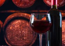 Wine glass near bottle in old wine cellar background Royalty Free Stock Photos