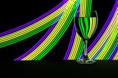 Wine glass with neon light behind royalty free stock image