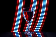 Wine glass with neon light behind stock photo