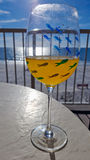 Wine glass with ocean background. Wine glass on table with ocean beach in background stock photo
