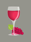 Wine in a Glass. Red wine in a glass with a bunch of grapes, isolated on a gray background Stock Photos