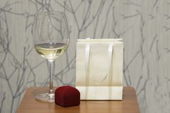 10b24cb80d Wine glass and red jewerly box on wooden table over grunge wall. Holiday  background.