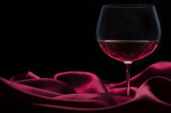 Wine. Glass of wine on red silk with dark background Stock Images