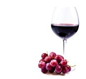 Wine glass with red wine. And grapes isolated over white background Royalty Free Stock Images