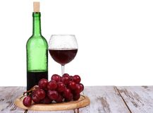 Glass with red wine, bottle of wine and grapes isolated over white background. Wine glass with red wine, bottle of wine and grapes on board isolated over white stock images