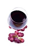 Wine glass with red wine and grapes. Isolated over white background Stock Photo