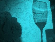 Wine Glass Silhouette in Blue. Photograph taken of a shadow of a partially-filled wine glass, cast on a textured wall (Adelaide, Australia royalty free stock photo