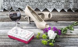 Wine glass sitting beside pair of high heels on wood floor. Horizontal image of a pair of shoes lying on a wood floor beside a glass of wine and some flowers Stock Photos