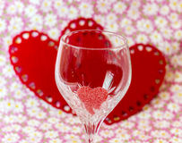 Wine glass with sugar candy red heart inside, pink floral backgr Stock Images