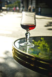 Wine glass on table. A view of a wine glass partially filled with red wine, sitting on the edge of a table at an outdoor French cafe Stock Photos
