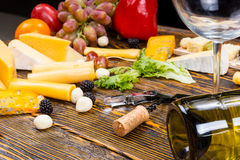 Wine Glass on Table with Gourmet Cheeses and Fruit Royalty Free Stock Photos