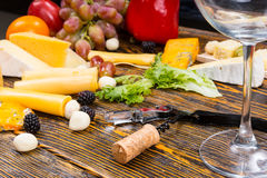 Wine Glass on Table with Gourmet Cheeses and Fruit Stock Images