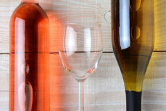 Wine Glass Between Two Bottles. Closeup of a wine glass between a bottle of red wine and a bottle of white wine. All three objects are laying on a rustic white Royalty Free Stock Photos