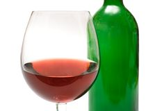 Wine Glass w/ Background Bottle. Glass of wine in front of an empty wine bottle Stock Image