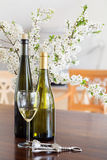 Wine glass and white wine bottles in front of a blurred bouquet Royalty Free Stock Photos