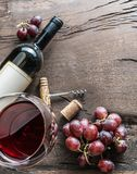 Wine glass, wine bottle and grapes on wooden background. Wine ta Royalty Free Stock Photo