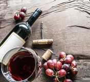 Wine glass, wine bottle and grapes on wooden background. Wine ta Stock Photos