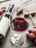Wine glass, wine bottle and grapes on wooden background. Wine ta Stock Photography
