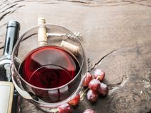 Wine glass, wine bottle and grapes on wooden background. Wine ta Stock Image