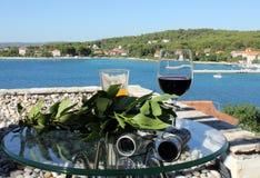 Wine 9105. Glass of wine and laurel branch with mediterranean village in background, island Zlarin, Croatia stock photo