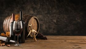 Traditional winemaking and wine tasting. Wine glass, wooden barrel and collection of excellent red wine bottles in the cellar: traditional winemaking and wine Stock Image