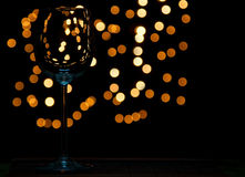 Wine glass on wooden table with dark and bokeh background. Distant lights Royalty Free Stock Photo