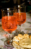 Wine Glasses. Still life photograph of two decorative glasses of wine with etched winter scenes on a table with a plate of brie cheese and crackers Royalty Free Stock Photos