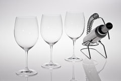 Wine Glasses. 3 Red or white wine glasses with a bottle of wine in wine holder Stock Images