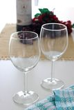 Wine glasses. Empty wine glasses with bottle of wine and some grapes in the background royalty free stock images
