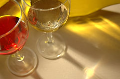 Wine Glasses. Two wines glasses with reflections in foreground from light through wine bottle royalty free stock photo