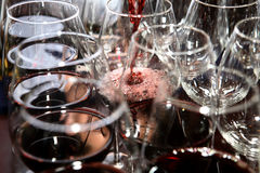 Wine in glasses. Red wine being poured in glasses Stock Photos