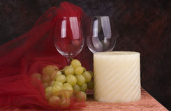 Wine glasses and accessories. Set of crystal wine glasses with grapes, candle and netting accessories. Sitting on a tabletop against a dark background royalty free stock images