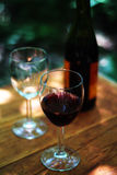 Wine glasses and bottle. Outdoor shot of two wine glasses and bottle set on a wooden table stock photography