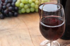 Wine Glasses & Bottle, Grapes on Wooden Table Royalty Free Stock Images