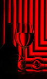 Wine glasses and bottle on red. Dark silhouette of wine glasses and a bottle of wine silhouetted on a bright red background with pleated right angles Royalty Free Stock Photo