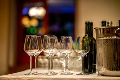 Wine glasses, bottles and ice bucket on table stock images