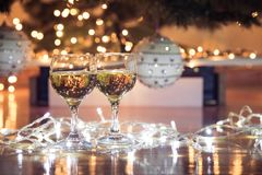 Wine glasses with bubbly drink for celebration toast wrapped in a Christmas light. Decorated christmas tree in the background. Holiday concept royalty free stock image