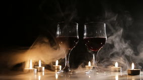Wine glasses and burning candles in the smoke. Two glasses of wine on black background and burning candles in the smoke..Glasses of red wine over candlelight stock footage