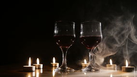 Wine glasses and burning candles in the smoke. Two glasses of wine on black background and burning candles in the smoke. Glasses of red wine over candlelight stock video