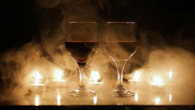 Wine glasses and burning candles in the smoke. stock footage