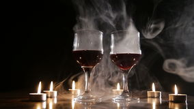 Wine glasses and burning candles in the smoke. Two glasses of wine on black background and burning candles in the smoke.Red wine glasses.Glasses of red wine stock video