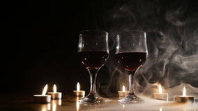 Wine glasses and burning candles in the smoke. Two glasses of wine on black background and burning candles in the smoke.Red wine glasses.Glasses of red wine stock footage