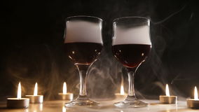 Wine glasses and burning candles in the smoke. Two glasses of wine on black background and burning candles in the smoke.Red wine glasses.Glasses of red wine stock video footage