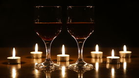 Wine glasses and burning candles. Two glasses of wine on black background and burning candles.Glasses of red wine over candlelight and darkness.focus bokeh stock video footage