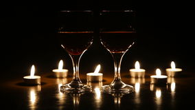 Wine glasses and burning candles. Two glasses of wine on black background and burning candles.Glasses of red wine over candlelight and darkness.Romantic stock video